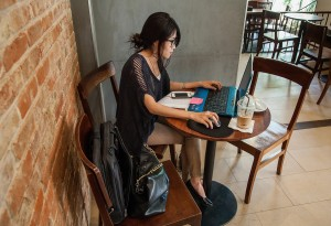 "PHNOM PENH, CAMBODIA - APRIL 09:  A young Cambodian woman uses her laptop in a local restaurant on April 9, 2014 in Phnom Penh, Cambodia. Leaked to the media for the first time on 9 April 2014, the draft of Cambodia's first-ever cybercrime law, in the pipelines since May 2012, is being criticised by international and local human rights organisations for severely restricting freedom of expression online. Article 28 in particular is being criticised for including vague provisions that could be used to silence Cambodian citizens, such as Article 28(3), which prohibits publications ""deemed to generate insecurity, instability and political cohesiveness,"" and Article 28(4), which prohibits publications which ""slanders or undermined the integrity of any governmental agencies."" Both of these provisions carry with them sentences of 1 to 3 years in prison. Internet penetration has drastically increased in recent years and is increasingly serving as an outlet and as a source of information in a country where most media are controlled by the ruling party. Cambodia's government is already under criticism for recent crackdowns on protests and human rights activists, and is accused of frequently using provisions in the Criminal Code and other legislation to unjustly silence civil society and journalists. Human rights activists fear that this new law will exacerbate the situation and provide the government with additional tools to silence its critics online. (Photo by Omar Havana/Getty Images)"